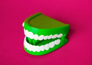 Artificial teeth and dental implant supported dentures