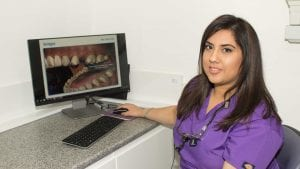 Dr Kiran Mandair sitting by computer with picture of teeth